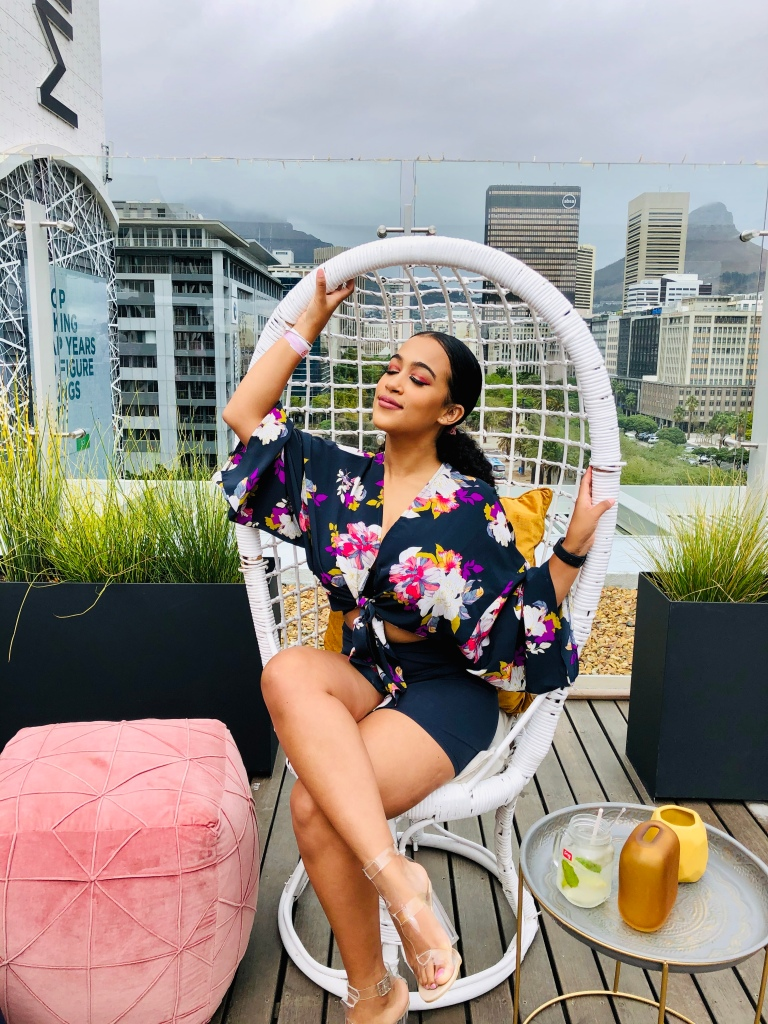 Nadine is seated on a rooftop location with city views behind her of the Beautiful Cape Town. She's wearing a floral top with Bicycle Shorts. Her hair is in a slick, low ponytail.